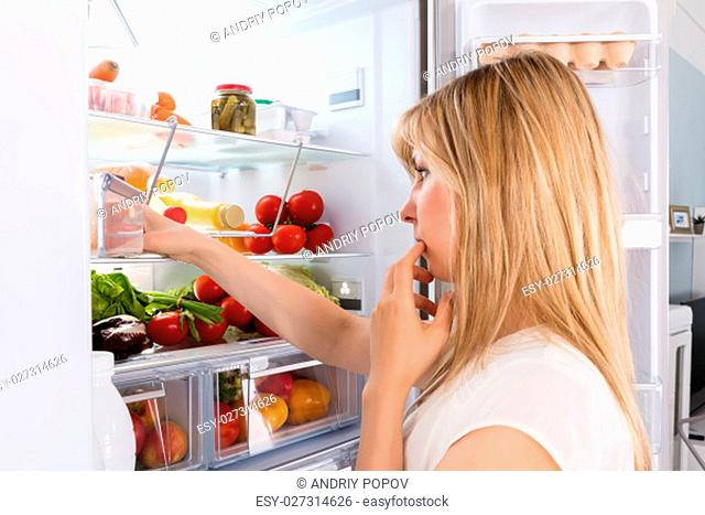 Young Woman Looking In Fridge At Kitchen