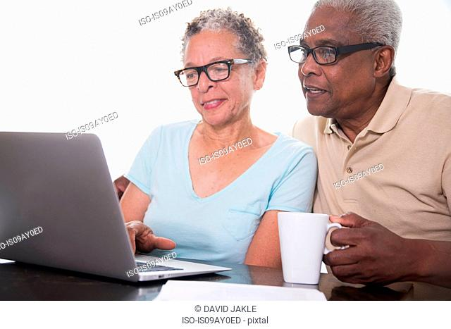 Senior couple sitting at table, using laptop