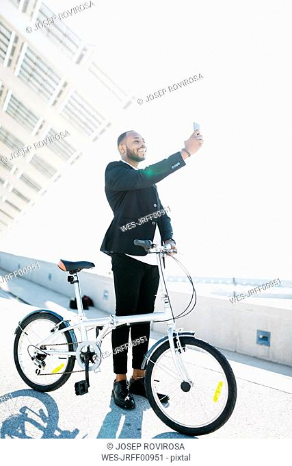 Smiling businessman with bicycle taking a selfie