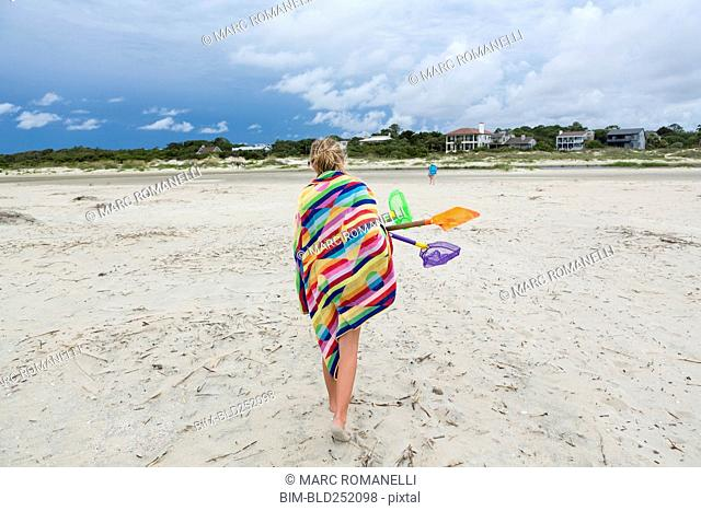 Caucasian girl walking on beach carrying net and shovels