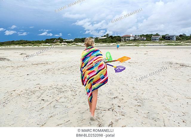 Caucasian girl walking on beach carrying net and shovels