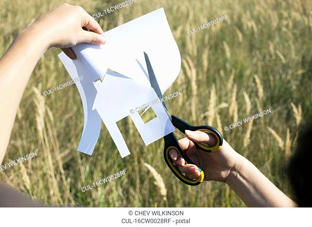 Hands cutting paper house