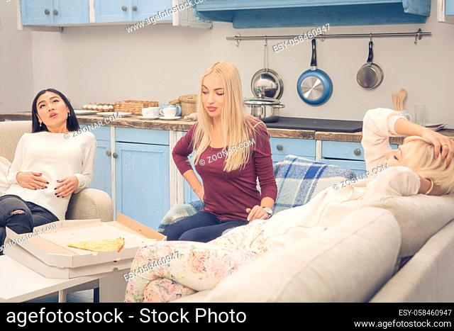 Home party concept. Toned picture of beautiful ladies ready to sleep after rest or relax. Friends girls resting after eating delicious pizza while having party...