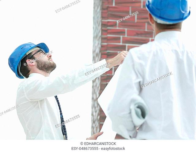 business background.architect and foreman looking at a house under construction