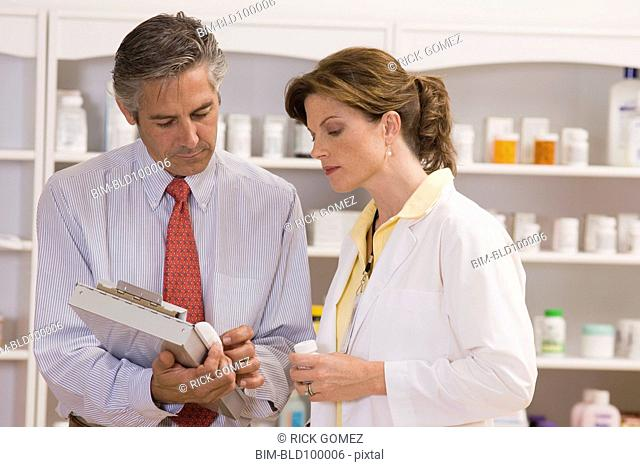 Caucasian co-workers working in pharmacy
