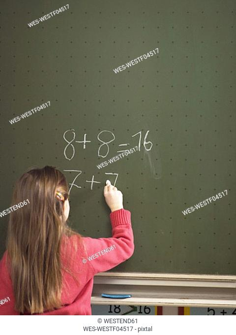 Girl standing in front of blackboard, solving arithmetic problem, rear view