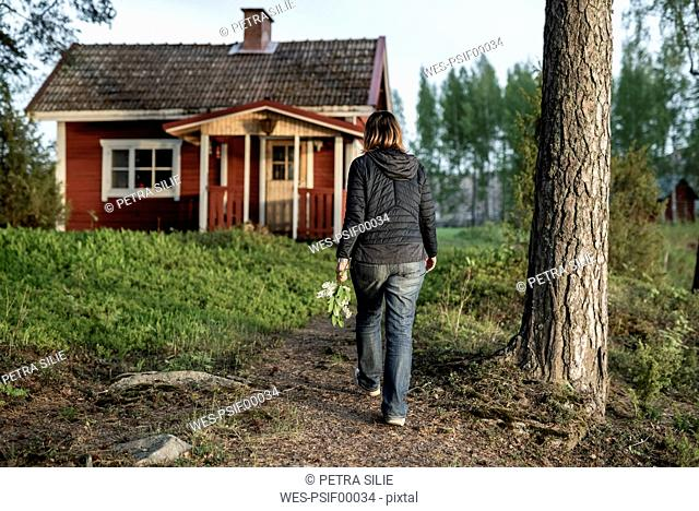 Finland, Kuopio, woman walking at a cottage in the countryside