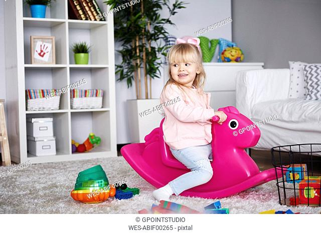 Portrait of smiling little girl sitting on pink rocking horse in the living room