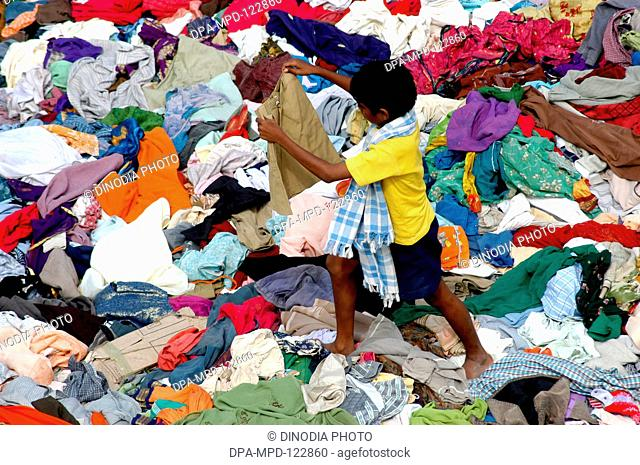A boy selecting pants for himself from the stacks of clothes that arrived Nagapatinam following the Tsunami disaster as help from the people of the country as...