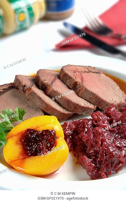 Venison loin roasted with red cabbage and peach stuffed with blueberries