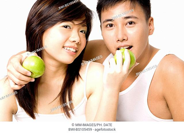 A pretty looking Asian couple in white eating apples
