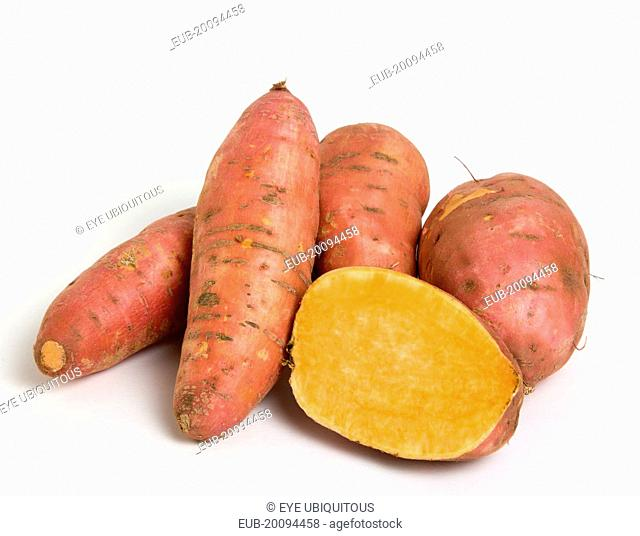 Group shot of North American sweet potatoes on a white background with on potato cut in half showing the orange coloured centre