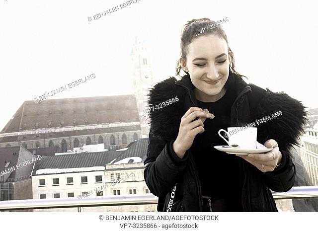 happy woman holding warm coffee cup outdoors in city next to touristic attraction Frauenkirche, Marienkirche, in Munich, Germany