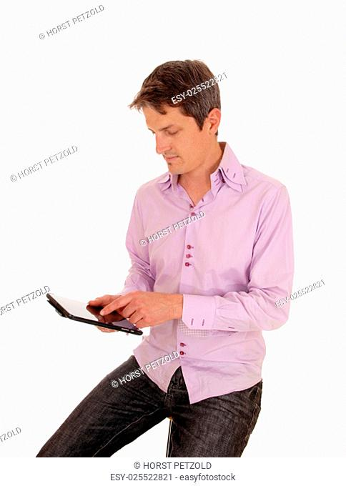 A young businessman sitting isolated for white background and working.on his tablet pc.