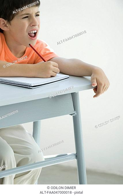 Elementary school student taking notes in classroom, squinting at board