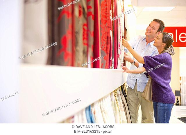 Caucasian couple examining fabric swatches in store