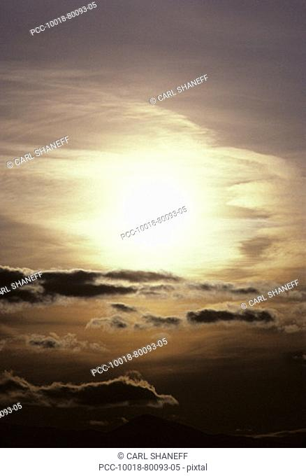 Glare of sun behind clouds in moody sunset sky