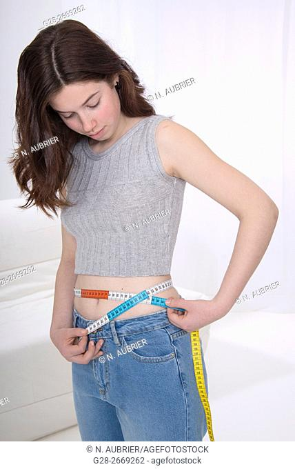 Teenage girl measuring her waistline with a tape measure, for dieting, anorexia