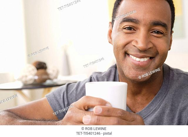 Portrait of smiling mature man holding mug
