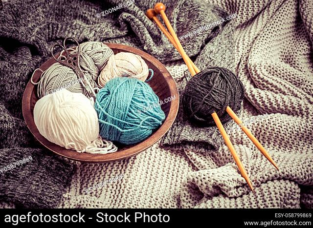 Home life - Knitting concept, knitting needles with blanket, scissors and yarn in wooden bowl