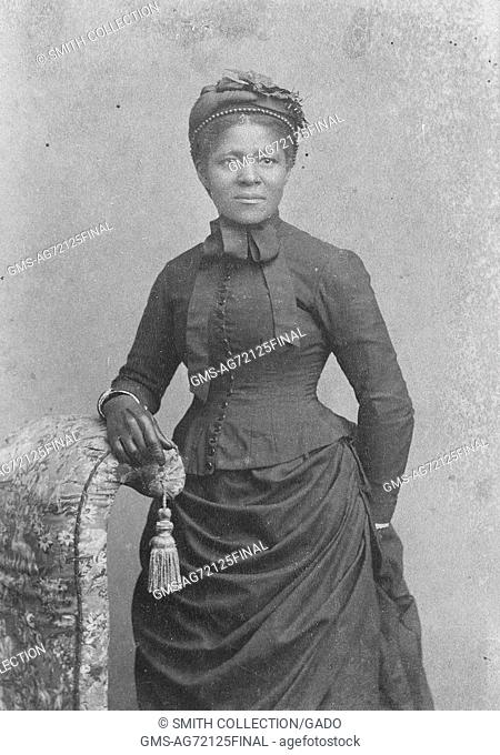 Sepia studio portrait of an African-American woman, three quarter length, wearing hat and gloves and dress with bustle, 1875