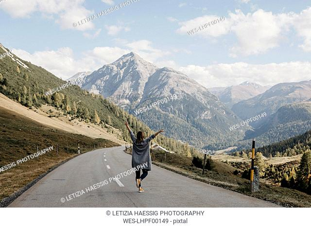 Switzerland, Engadin, rear view of happy woman with raised arms on mountain road