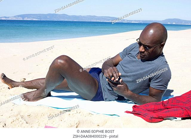 Man lying on beach, using smartphone