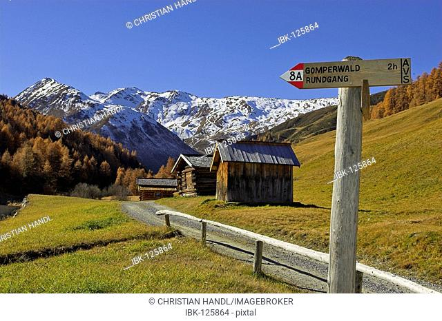 Signposts and wooden huts in the Vallung valley (end of the Rojen valley), South Tyrol, Italy