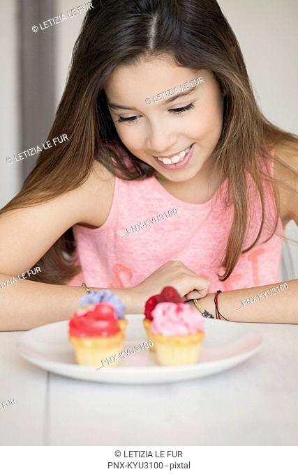 Happy girl with cupcakes