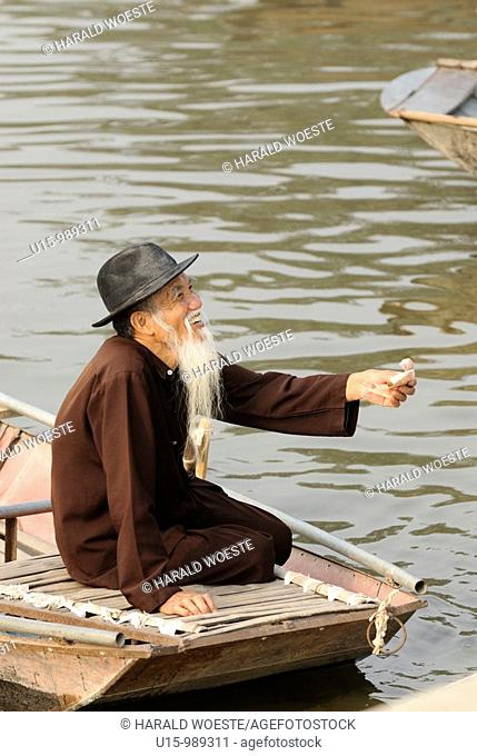 Asia, Vietnam, Tam Coc near Ninh Binh  Elderly vietnamese boat man at Tam Coc Three Caves receiving the trip fare  To visit the Three Caves Tam Coc tourists are...