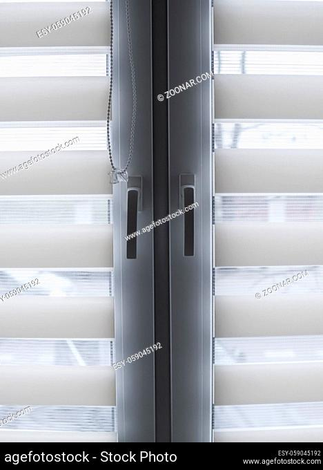 White fabric roller blinds on the white plastic window in the living room. Roll curtains indoor