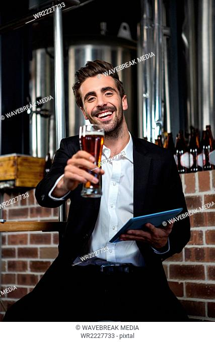 Handsome man holding beer and tablet