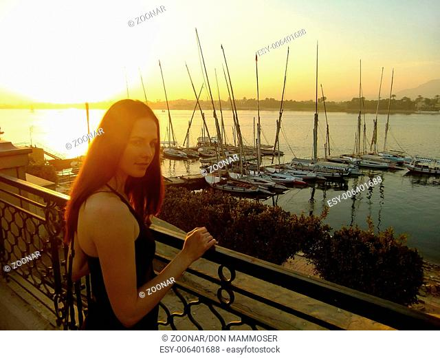 Young woman admiring sunset over the Nile river, L
