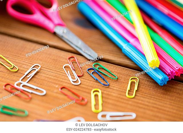 education, school supplies, art, creativity and object concept - close up of felt pens with clips and scissors on wooden table
