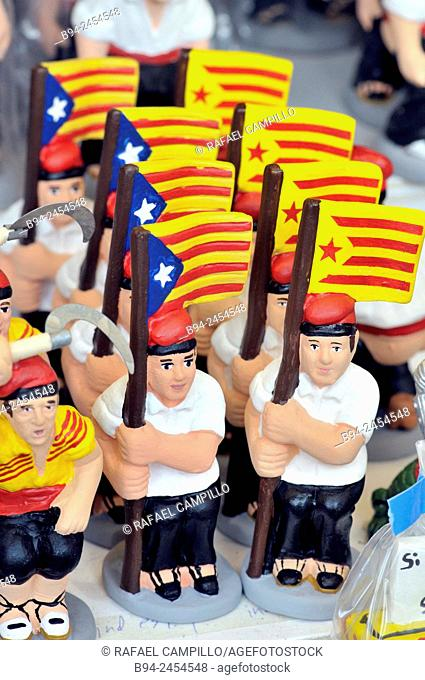 'Caganers', particular feature of modern nativity scenes at Santa Llucia Christmas fair, Catalonia independent flag, Barcelona. Catalonia, Spain
