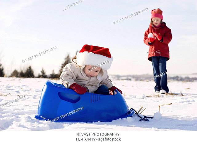 Boy Sitting in Sled, Sister in the Background with Snowball