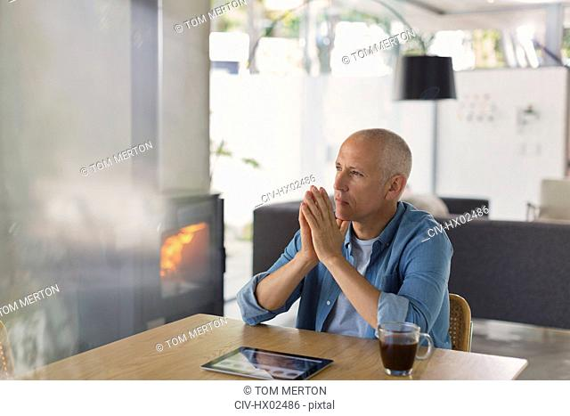 Pensive man with digital tablet drinking coffee and looking away near wood burning stove fireplace