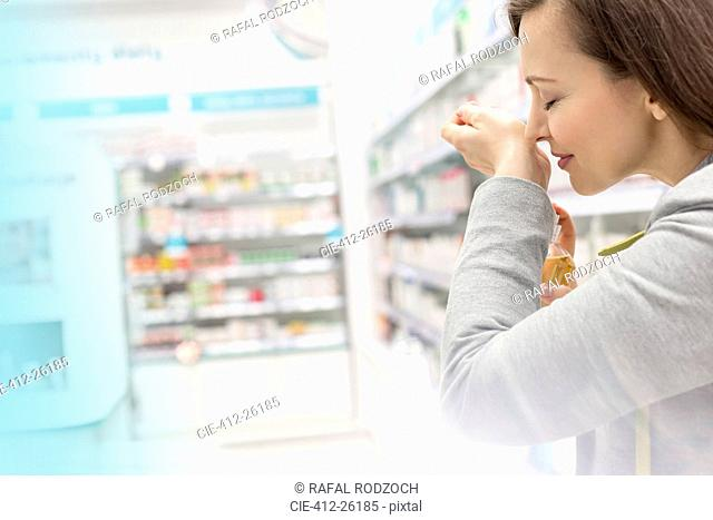 Woman trying on perfume in pharmacy