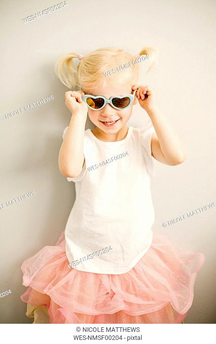 Portrait of blond little girl putting on heart-shaped sunglasses