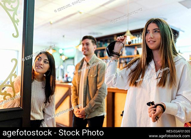 Teenager girl playing darts with friends in bar
