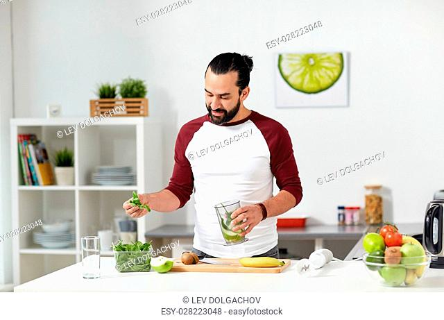 healthy eating, vegetarian food, diet and people concept - happy young man with blender cup and fruits cooking at home kitchen