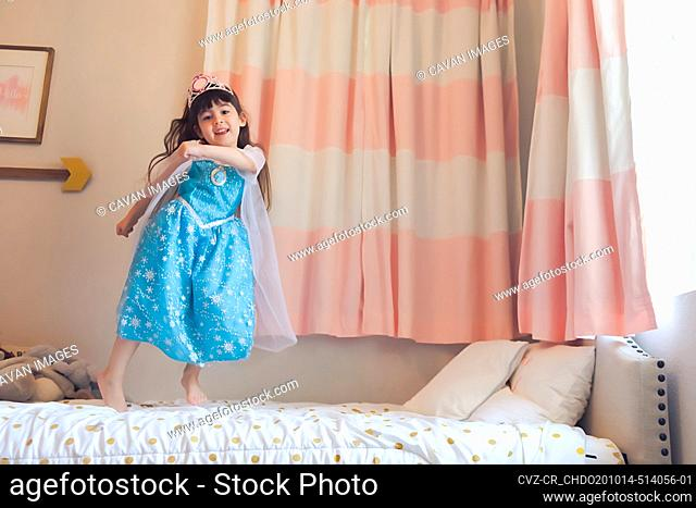 Little girl dressed as a princess dancing and jumping on her bed