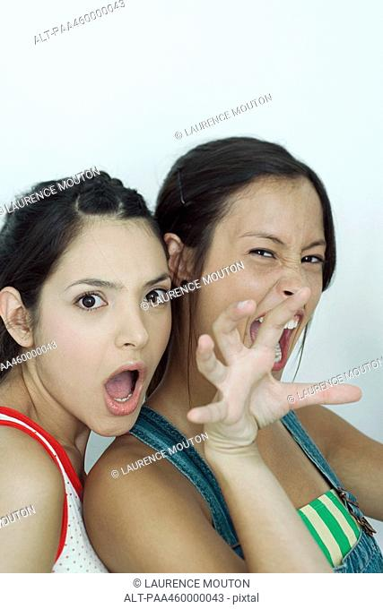 Two young female friends, one snarling at camera, the other with mouth open, portrait