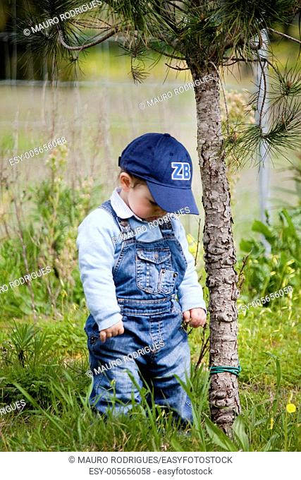 View of a young child next to a small tree