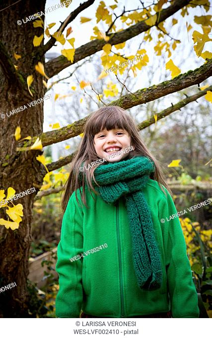 Portrait of grinning girl wearing green scarf and green jacket