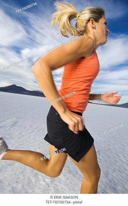 Woman running on salt flats, Utah, United States