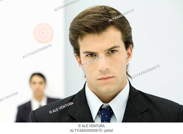 Young businessman frowning at camera, close-up
