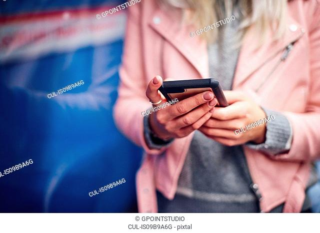 Mid section of young woman holding smartphone at city tram station