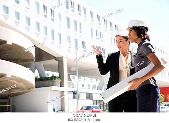 Two businesswomen, wearing hard hats, carrying plans