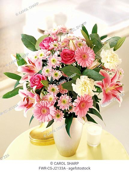 Lily, Lilium 'Star Gazer', Floral arrangement with pink chrysanthemum roses and carnations in a vase on a small table